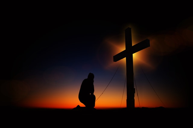 Man Kneeling in Front of Cross © Pixabay/pexels.com